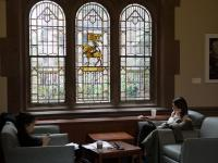 Student sitting by stained glass window